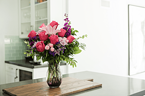 Teleflora's All Eyes on Her Bouquet- Lifestyle. Pink roses, lilies, and purple statics in purple ombre vase.