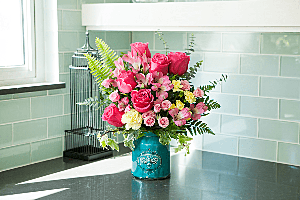 Teleflora's Country Beauty Bouquet- Lifestyle. Pink roses and alstromeria with yellow carnations in blue crock vase.